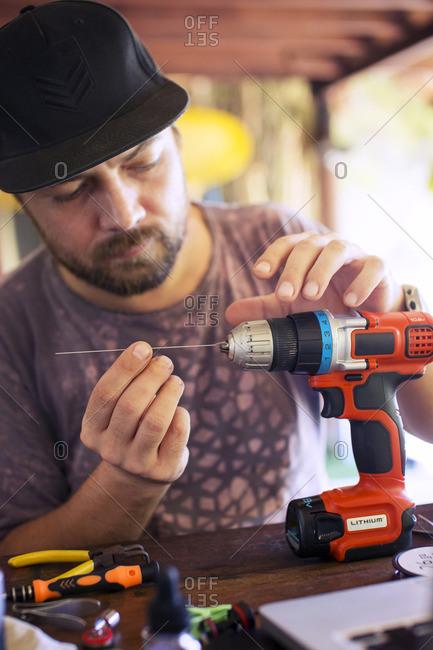 Man repairing drill in workshop