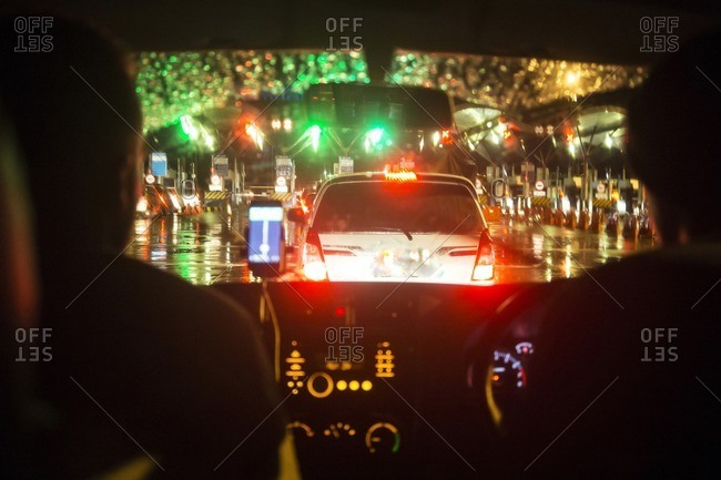 Cropped image of friends traveling in car against illuminated toll booth during monsoon