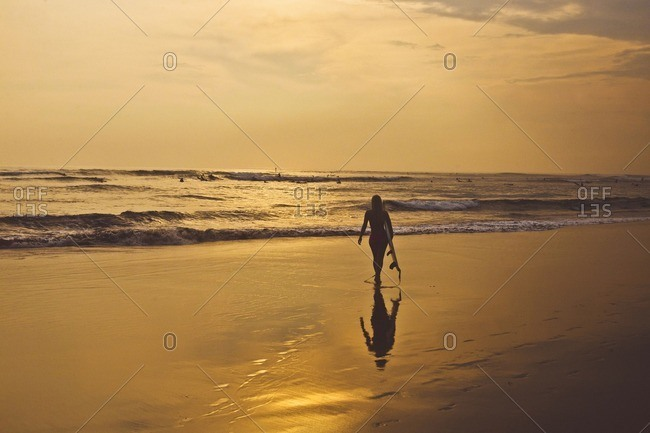 Silhouette woman with surfboard walking at beach