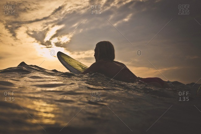 Woman surfing in sea against sky during sunset