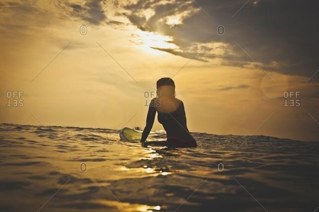 Woman sitting on surfboard in sea against sky