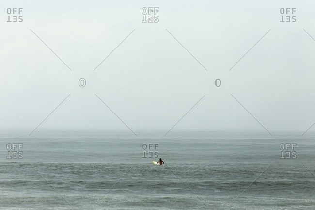 Man with surfboard in sea against sky during foggy weather