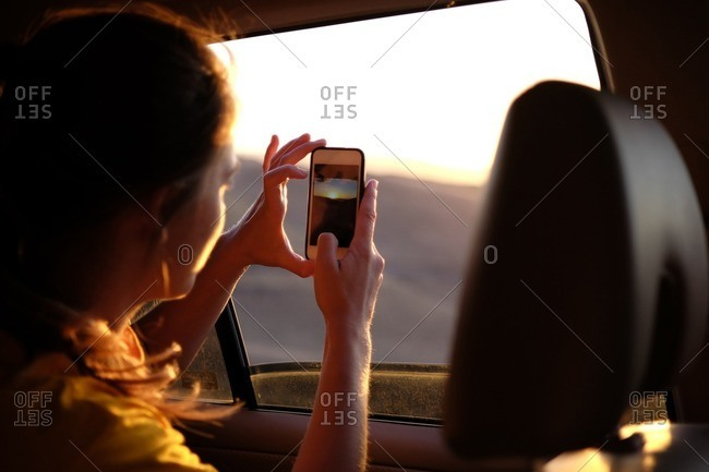 Woman in car photographing sky during sunset