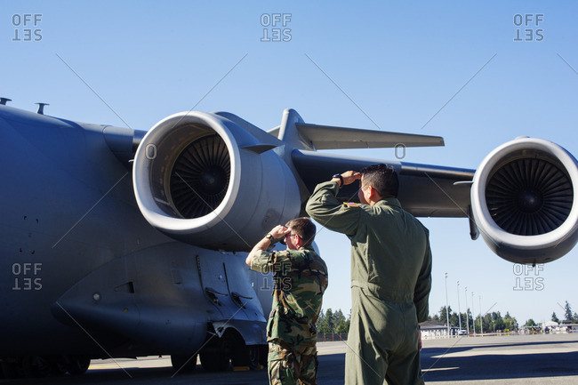 Army soldiers shielding while standing by military airplane on runway