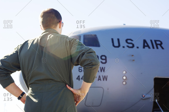 Low angle view of army soldier standing by military airplane on runway