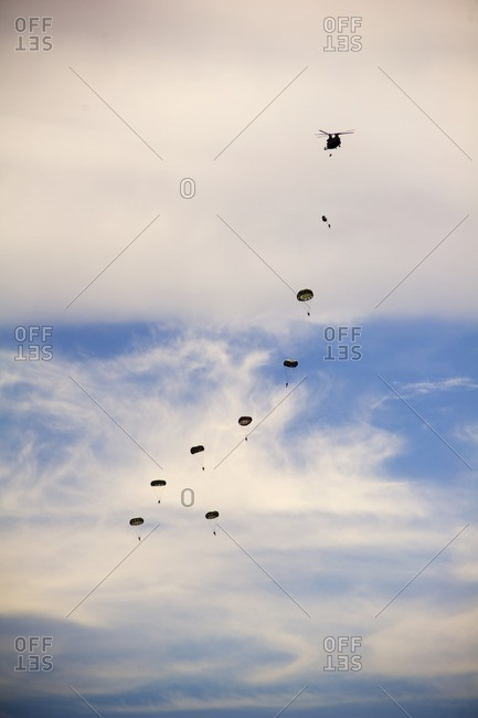 Low angle view of paratroopers flying in cloudy sky during airshow