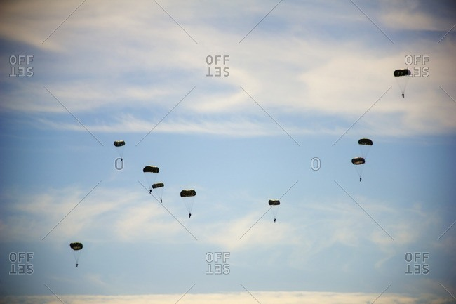 Low angle view of paratroopers flying in sky during airshow