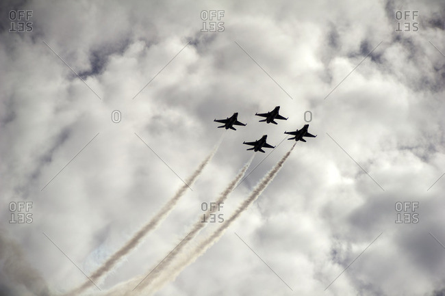 Low angle view of airshow in cloudscape