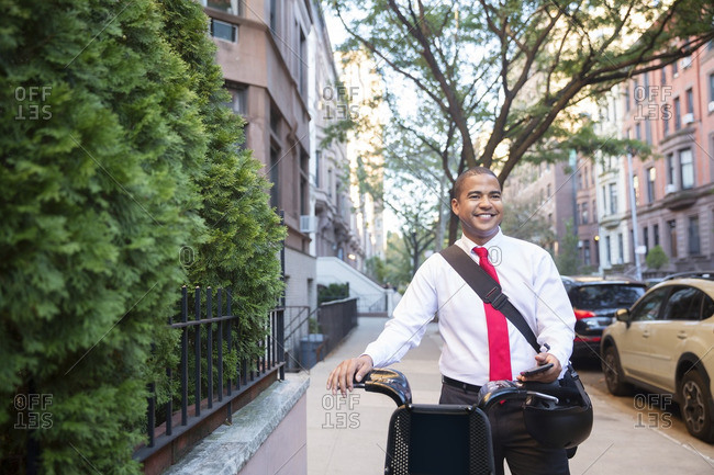 Happy businessman looking away while standing with bicycle on footpath