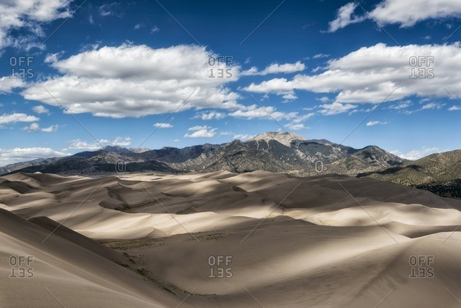 Scenic view of sand dunes against mountains