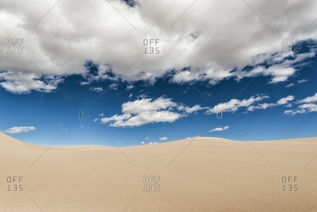 Desert landscape against cloudy sky on sunny day