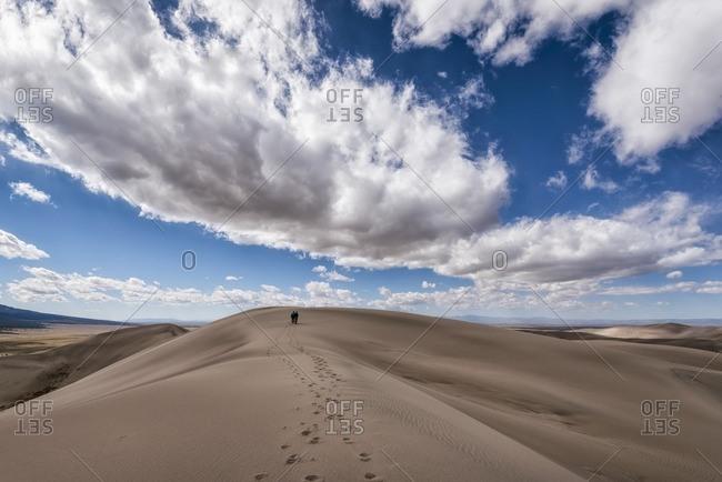 Distant view of people leaving behind footprints in desert
