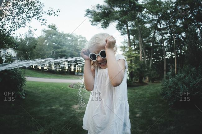 Water splashing over scared girl wearing sunglasses at backyard