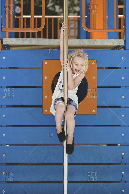 Cute girl playing on pole against wooden structure at playground