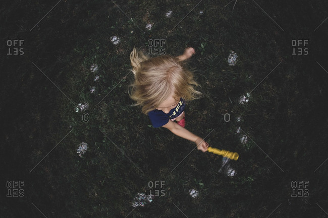 High angle view of girl playing with bubble wand on grassy field in backyard