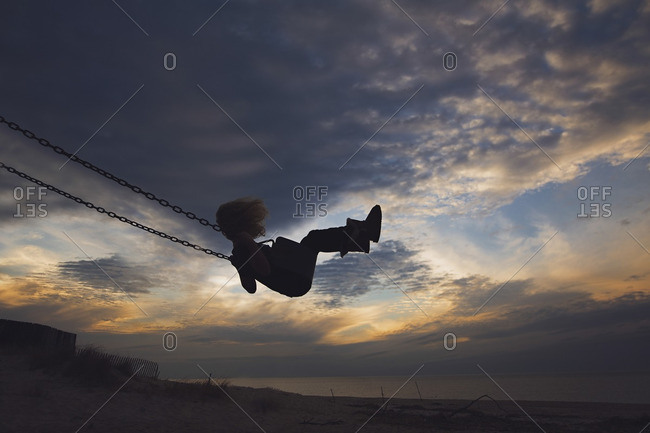 a771e40bedc8 Side view of girl playing on swing at beach against cloudy sky ...