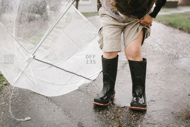 Girl in rubber boots holding umbrella while standing on wet road