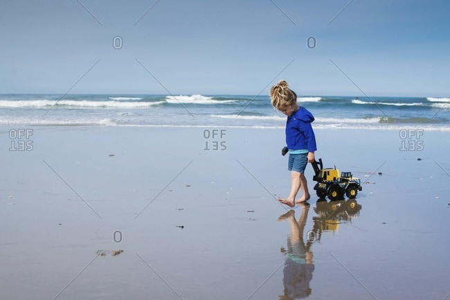 Girl pulling toy truck while walking at beach against cloudy sky