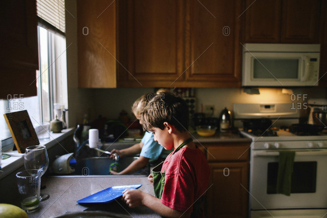 Siblings cleaning utensils in kitchen