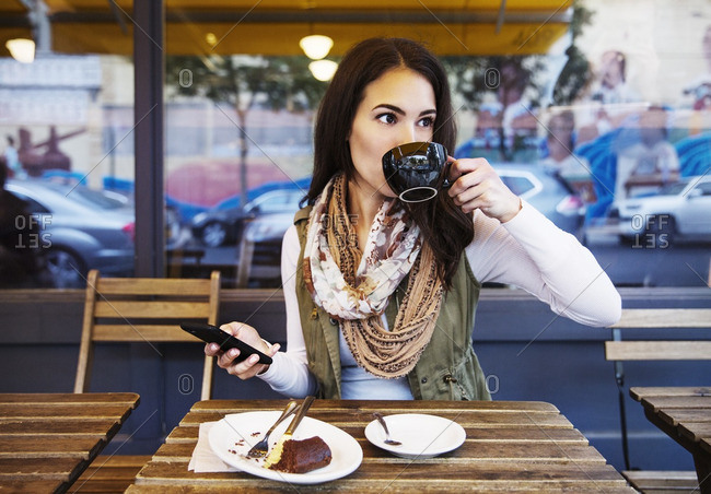 Woman holding mobile phone enjoying drink at cafe