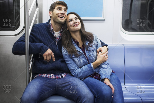 Happy couple traveling in train