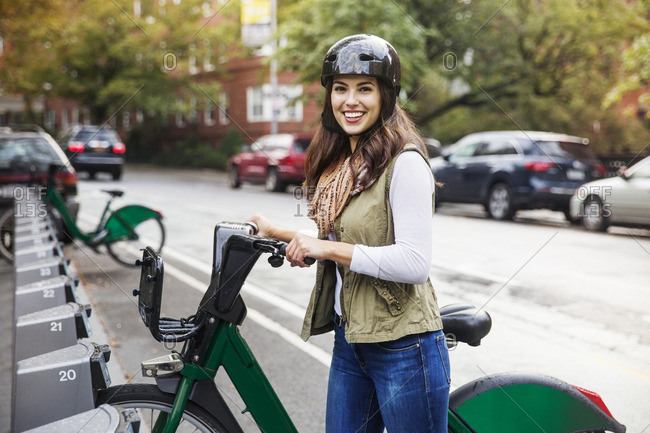 Portrait of smiling woman with bicycle standing at parking lot