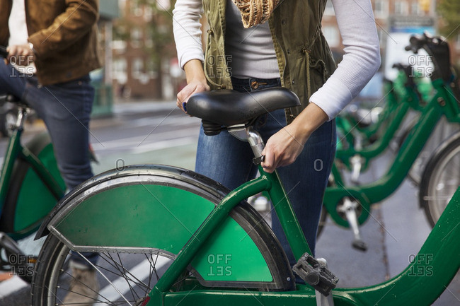 Midsection of woman adjusting bicycle seat while standing with boyfriend at parking lot