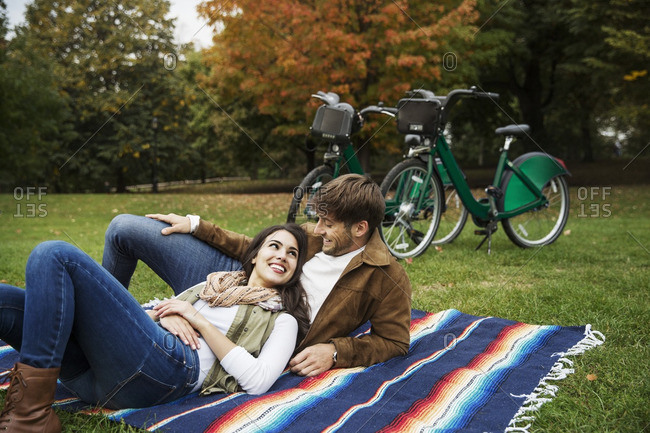 Happy couple looking at each other while relaxing on blanket in park