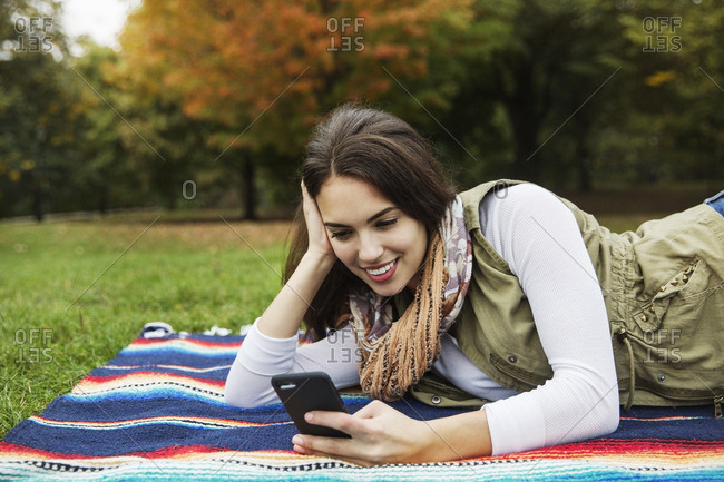 Happy woman using mobile phone while lying on blanket at park