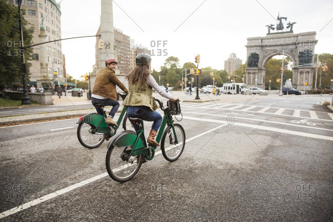 Couple riding bicycle on city street