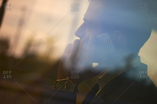 Businessman talking on mobile phone in office seen through glass