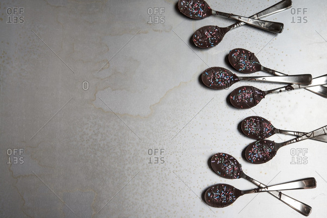 Overhead view of dessert in spoons arranged on table