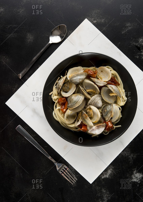 Overhead view of clams with linguine and tomato served in plate