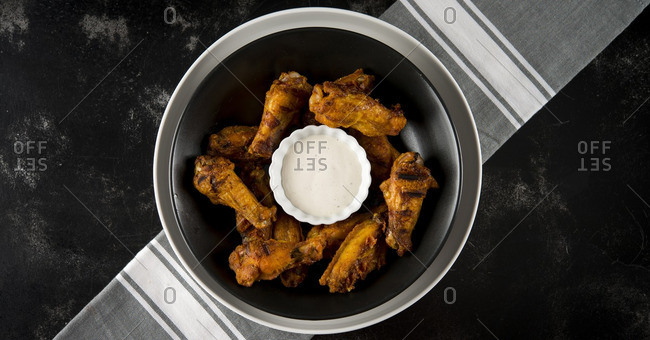 Overhead view of chicken wings in plate served on table