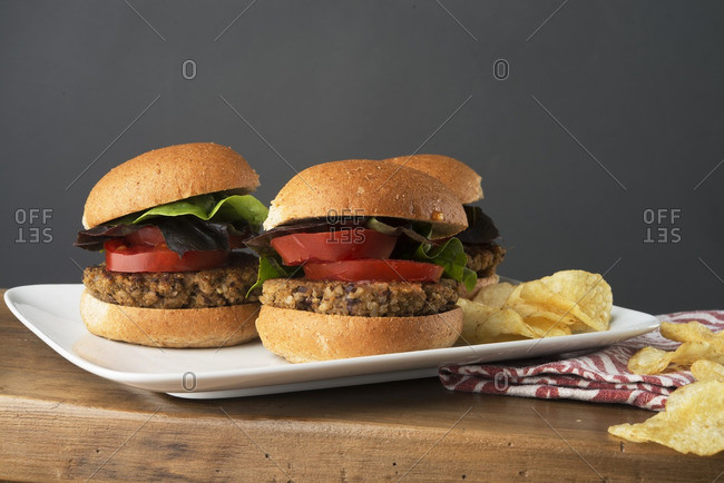 Close-up of veggie burgers with potato chips served on wooden table