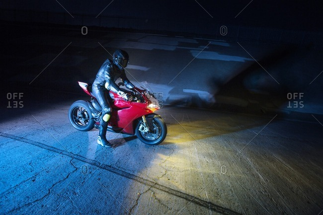 Biker with motorcycle on road at night