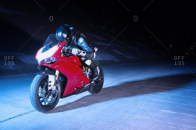Biker relaxing on motorcycle at night