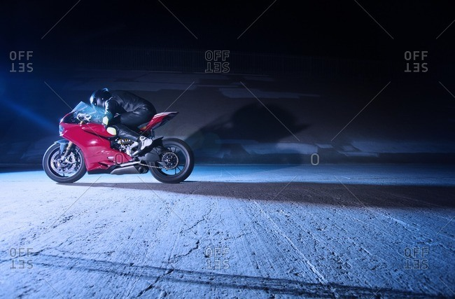 Biker relaxing on motorcycle by wall at night