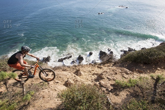 High angle view of athlete riding bicycle on rocky beach