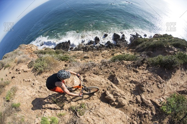 High angle view of athlete riding bicycle on rocks by sea