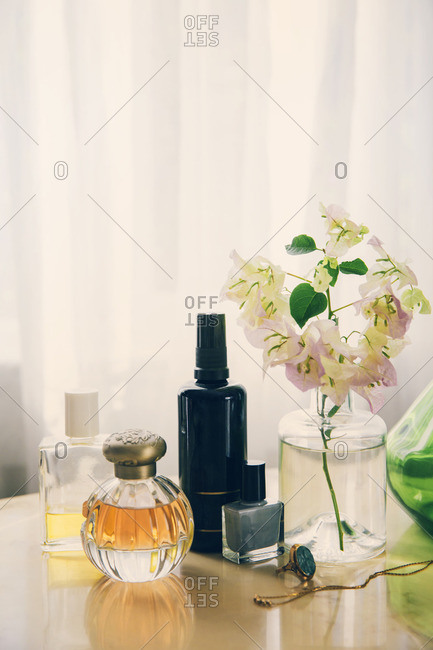 Beauty products with jewelry by flower vase arranged on table