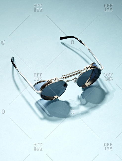 Round retro sunglasses on a light blue background