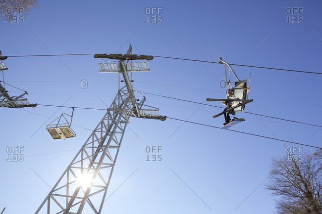 People in ski lift against blue sky