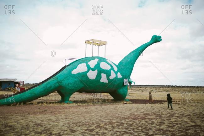 Kids by a dinosaur shaped slide