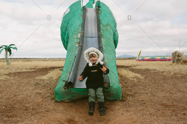 Girl on a dinosaur shaped slide