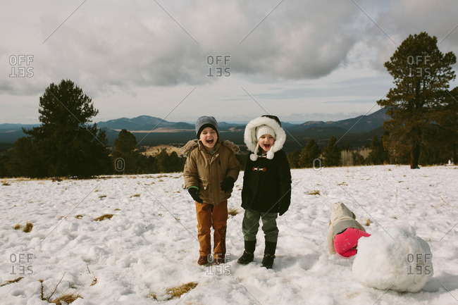 Laughing kids on a snowy hill