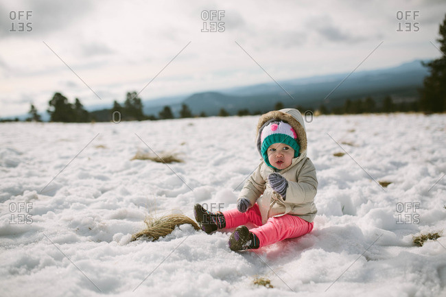 Toddler girl sitting in rural snow