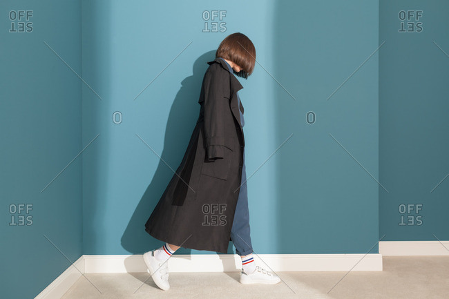 Young model wearing black trench coat in a blue room