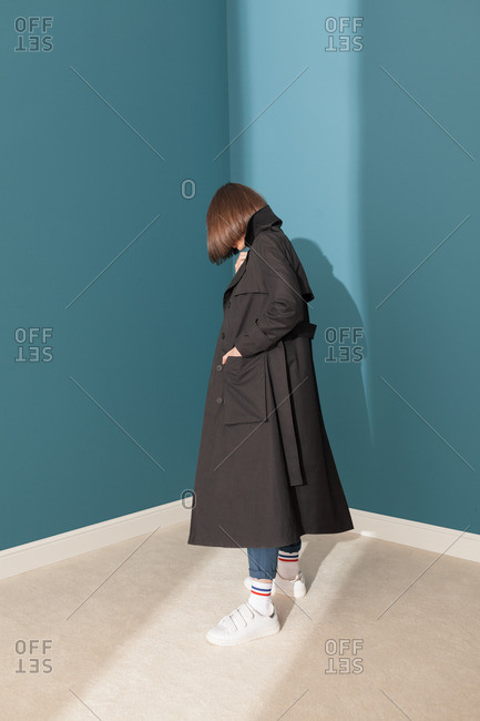 Young model with black trench coat in a blue room