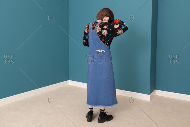 Woman wearing denim overalls dress with daisies in pocket